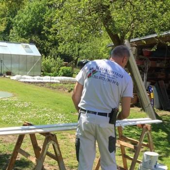 Maler Oliver Malchow beim Streichen einer Holzlatte in Weiß