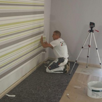 Maler Oliver Malchow beim Tapezieren